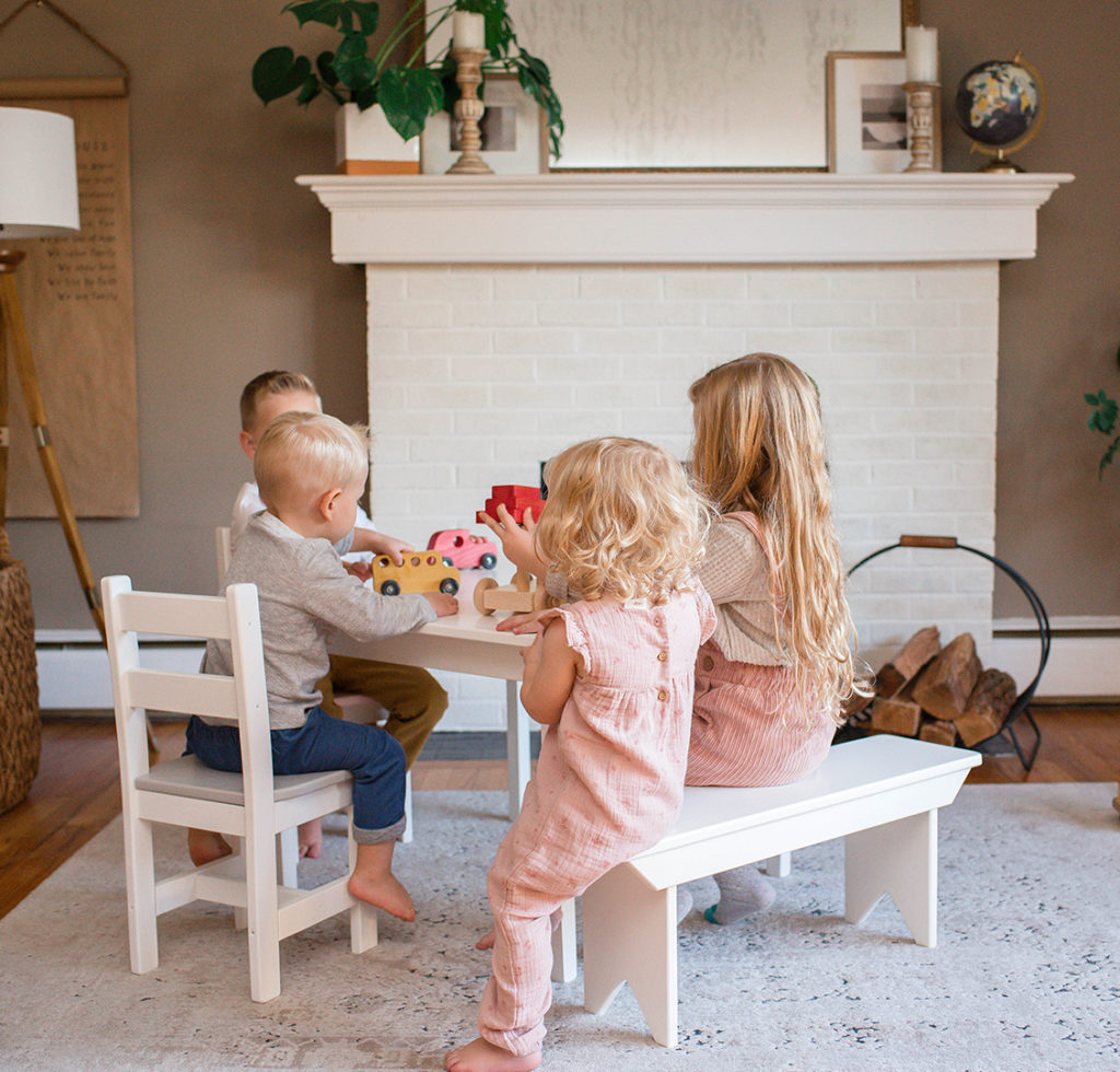 children sitting at white wooden table