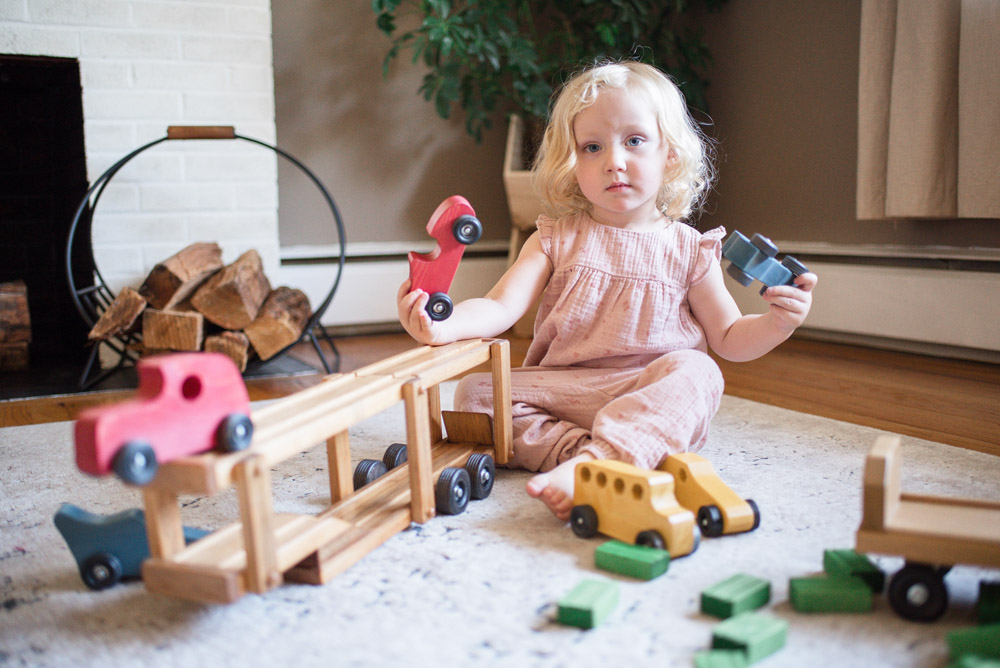Girl Playing with Wooden Car Carrier Toy