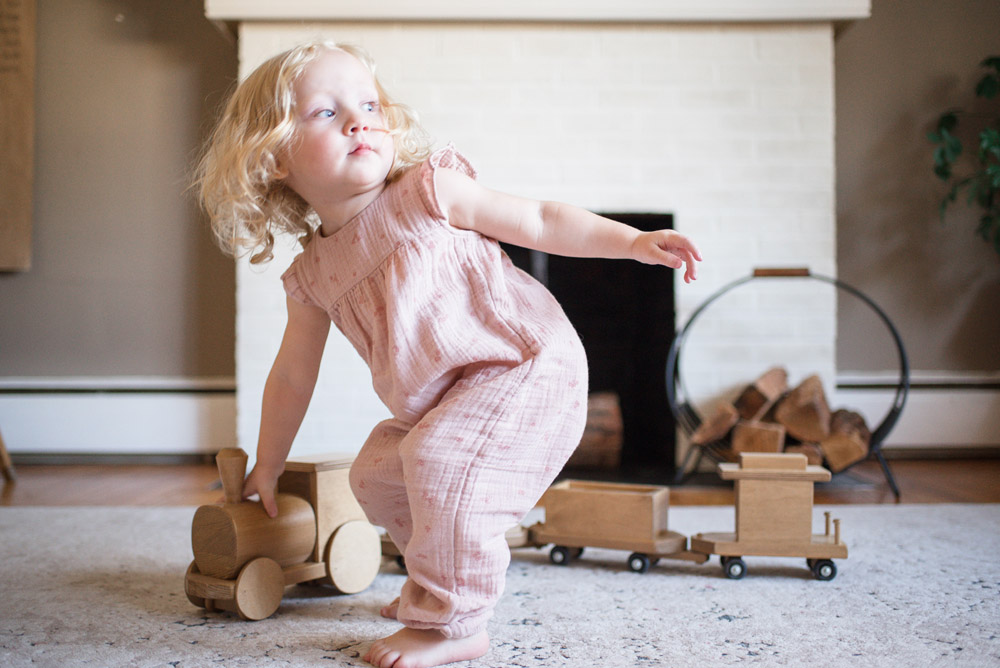 Girl Playing with Wooden Train Set
