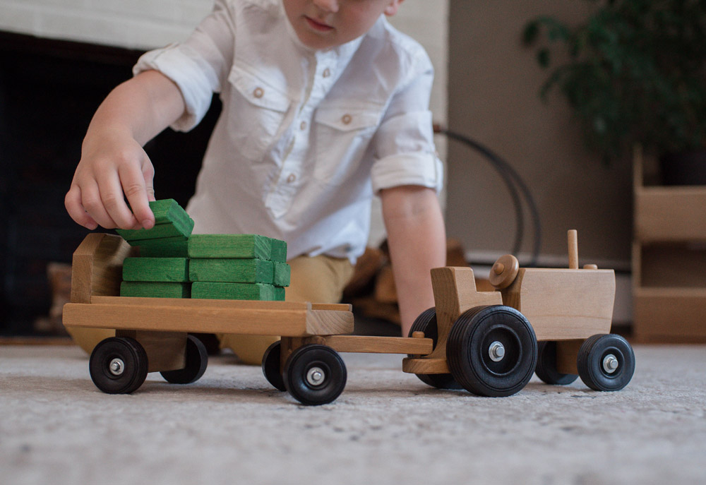 Boy playing with Wooden Tractor